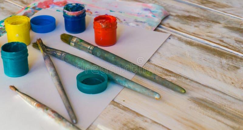 Рабочее место художника: краски акварели, кисти, листы белой бумаги, цветовая палитра и незаконченная картина стоковое изображение rf