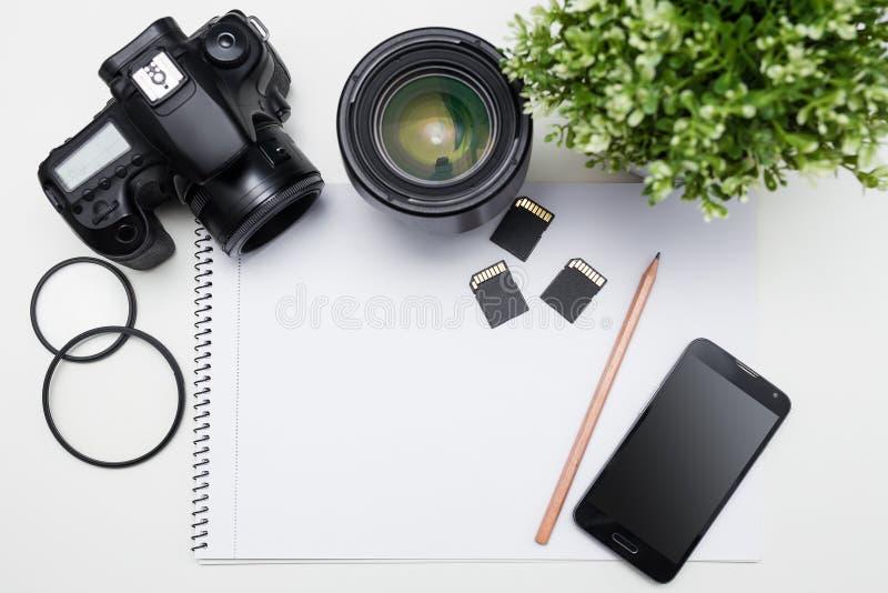 Рабочее место ` s фотографа - камера, оборудование фотографии, умное стоковое изображение
