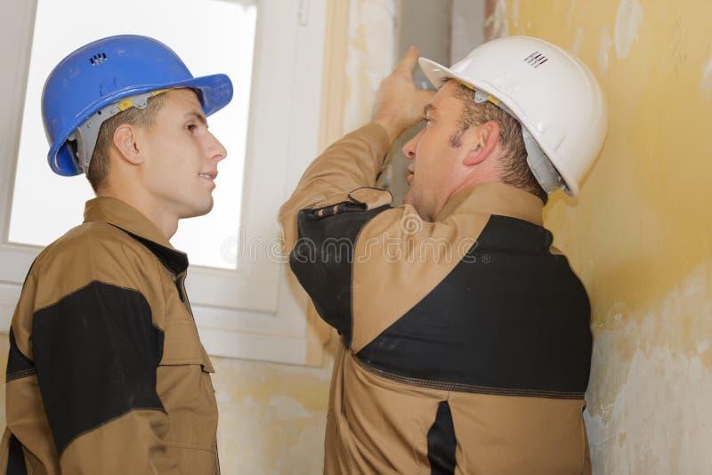 Рабочие классы с продукцией окон на строительной площадке стоковые фото