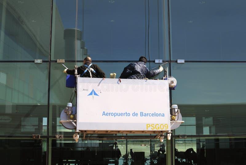 Рабочие классы очищая окна на авиапорте Барселоны. Испания стоковое изображение
