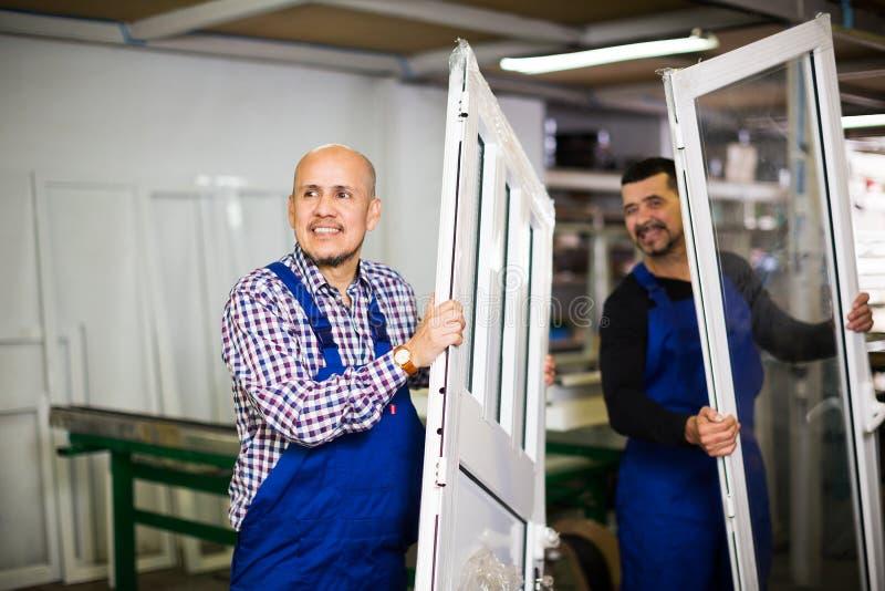 Рабочие классы с профилями и окнами PVC стоковое изображение