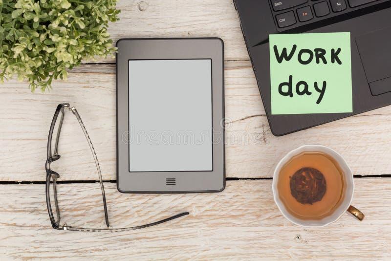 Рабочий день в офисе: компьтер-книжка, ebook, зеленый чай стоковое изображение