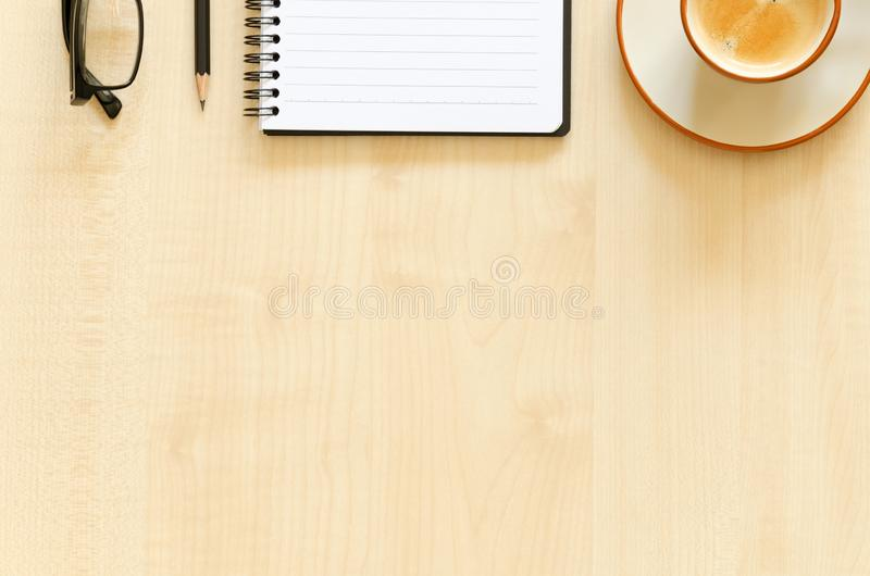 Рабочий стол с тетрадью, карандашем, eyeglasses и кофейной чашкой стоковые изображения