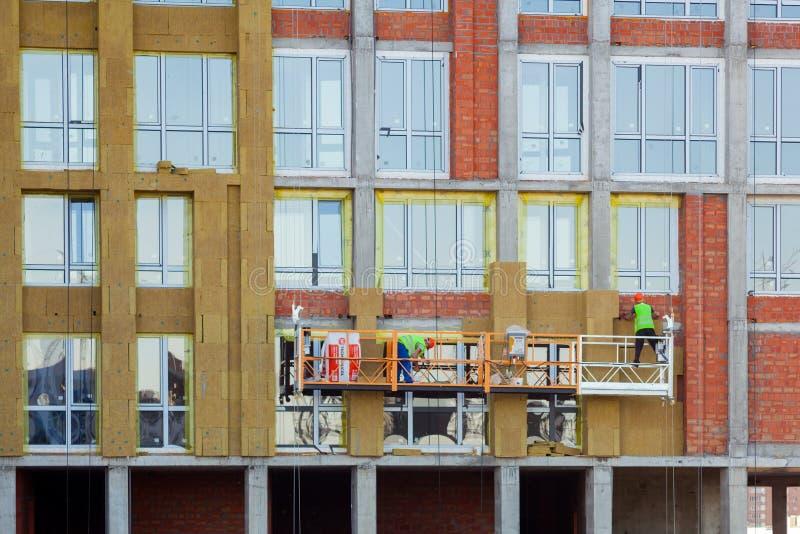 Рабочий-строители изолируя фасад дома с минеральной установкой шерстей утеса Внешняя система изоляции стены или minera EWIS стоковое изображение