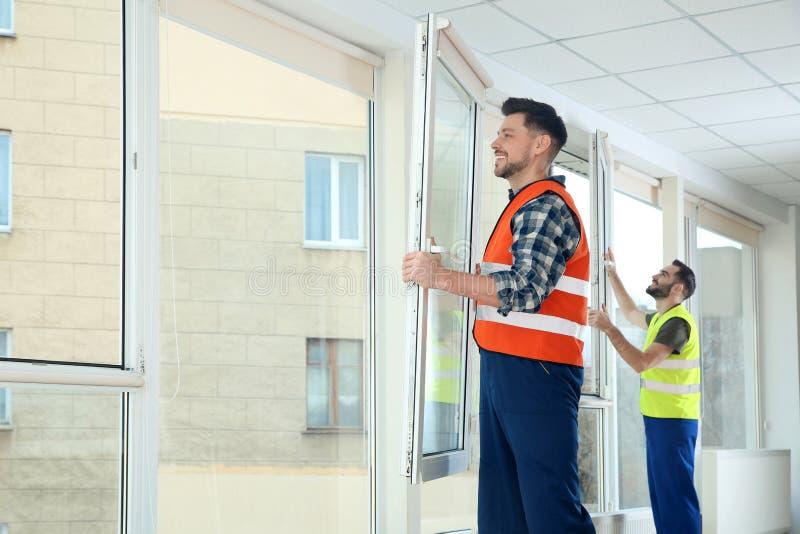 Рабочий-строители устанавливая пластиковые окна стоковые изображения rf