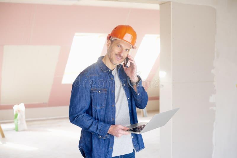 Рабочий-строитель используя компьтер-книжку и мобильный телефон стоковое фото rf
