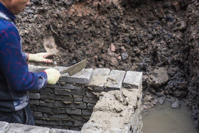Рабочий-строитель носящ голубые прозодежды держа носовой платок в дренажной траншее стоковая фотография