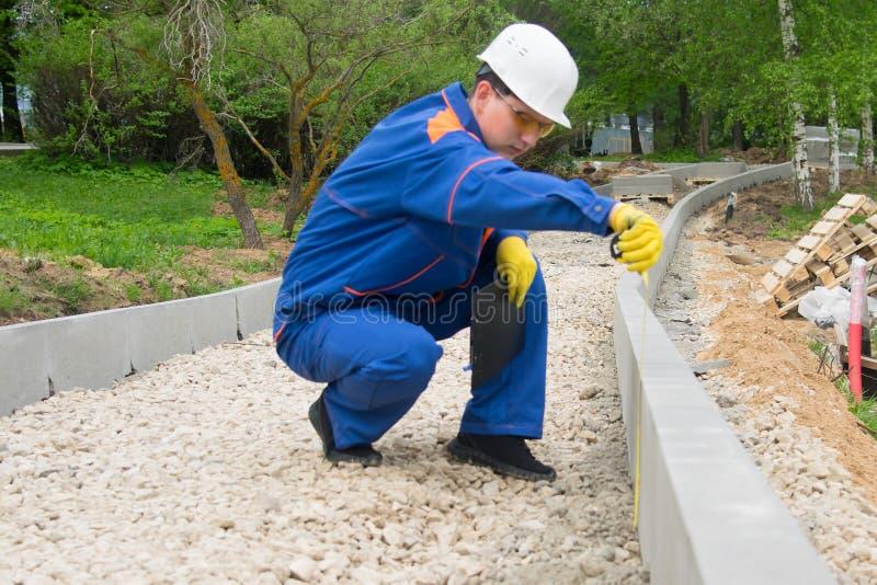 Рабочий-строитель проверяет прогресс класть насыпь уличного бордюра и щебня стоковая фотография rf