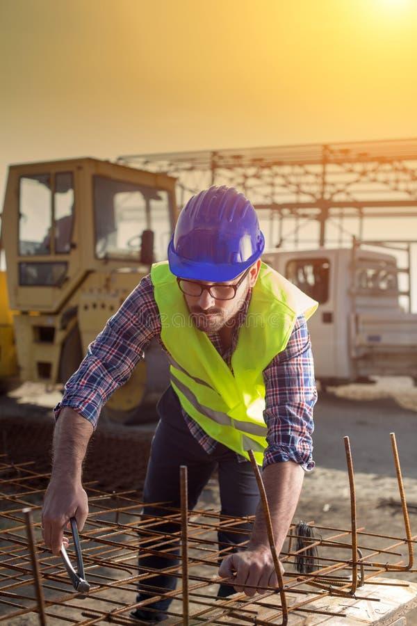Рабочий-строитель работая на сетке подкрепления стоковые фото