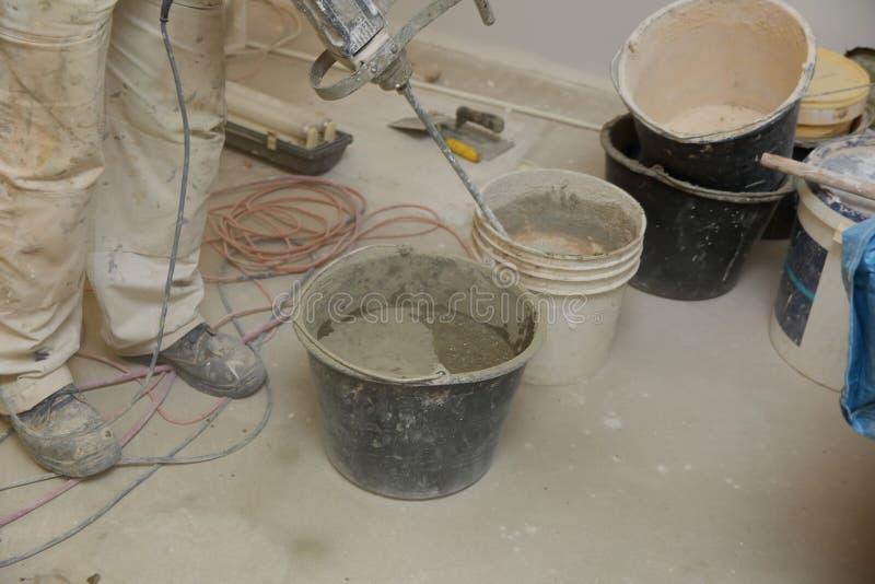 Рабочий-строитель смешивает прилипатель плитки вместе с водой в правильных пропорциях стоковые фото