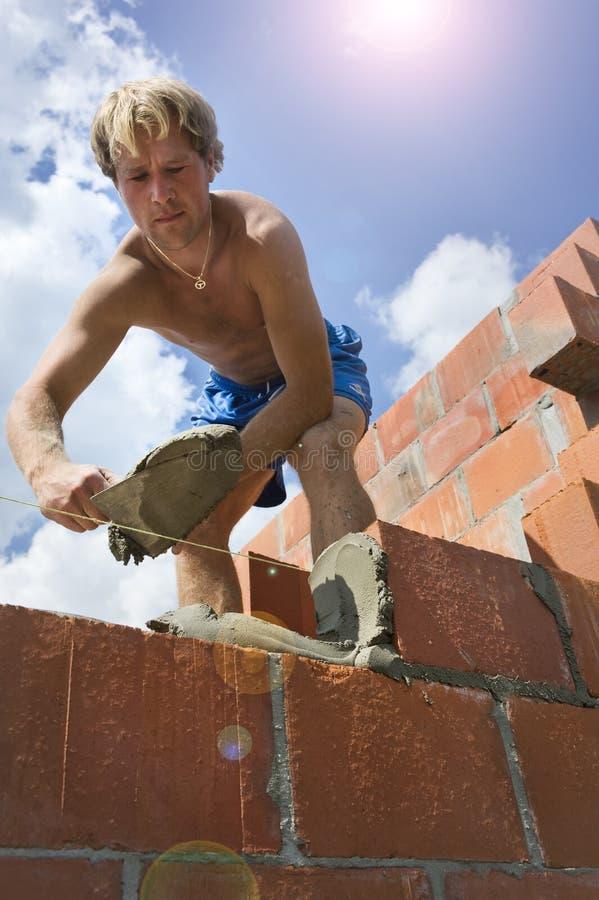 Рабочий-строитель строя стену стоковая фотография rf