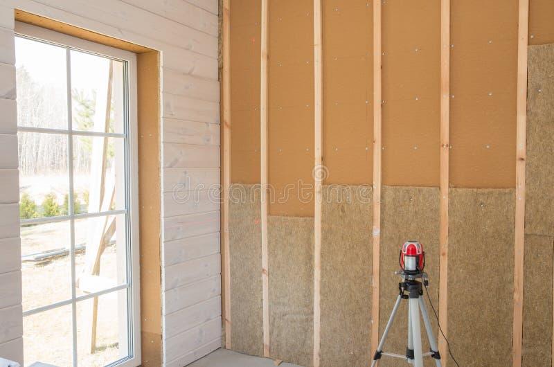Рабочий-строитель термально изолируя дом рамки эко-древесины с деревянными волокнистыми плитами и жар-изолируя естественную пеньк стоковая фотография