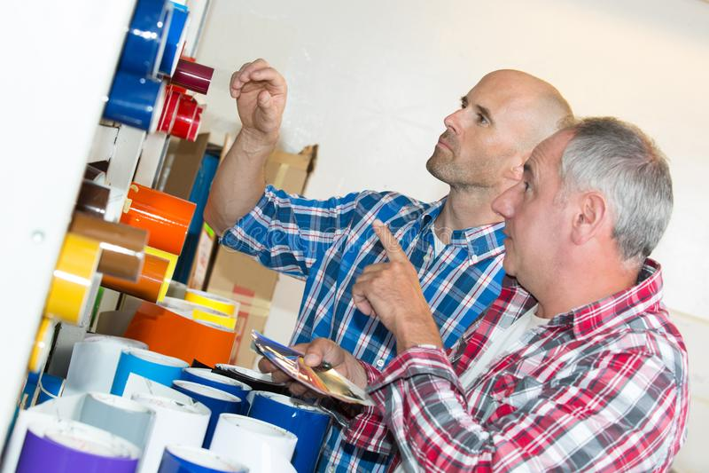 2 рабочий-строителя выбирая обои на магазине оборудования стоковая фотография
