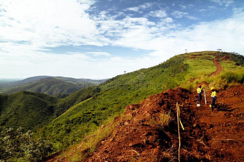 Рабочий-строители минирования исследуя верхней части горы в Африке стоковые изображения