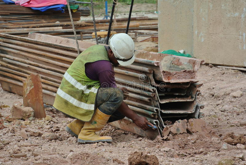 Рабочий-строители проверяя кучу листа стоковое изображение
