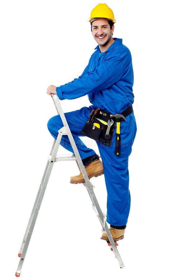 Рабочий-строитель взбираясь вверх лестница шага стоковые изображения rf