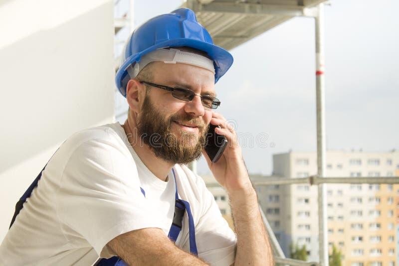 Рабочий-строитель в обмундировании работы и шлем на голове говоря на телефоне Работа на большой возвышенности Леса в задней части стоковые изображения