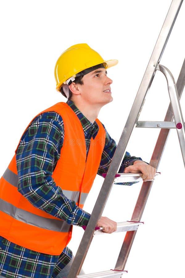 Рабочий-строитель в отражательной одежде взбираясь лестница. стоковая фотография