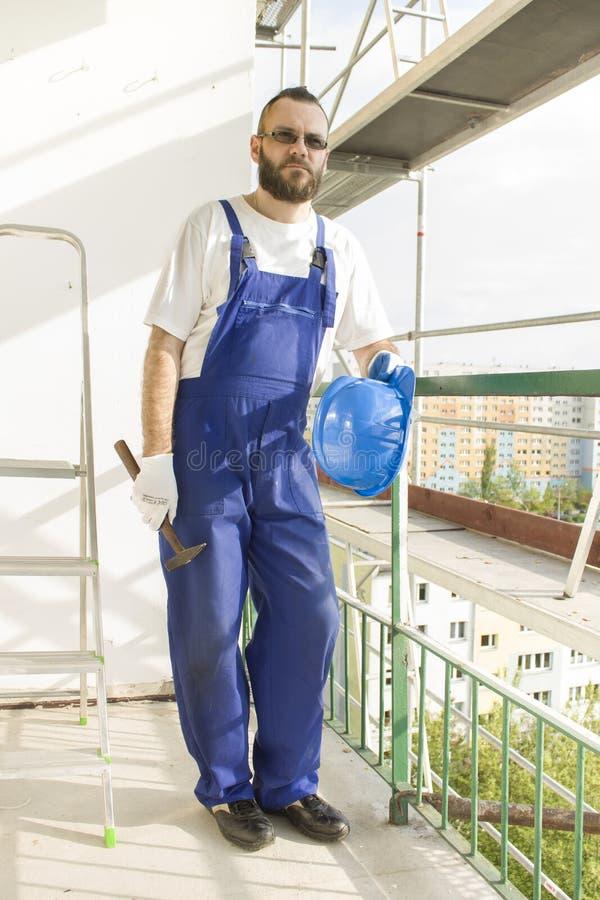 Рабочий-строитель в одежде работы, защитные перчатки держит шлем и молоток Работа на большой возвышенности Леса в b стоковые фотографии rf