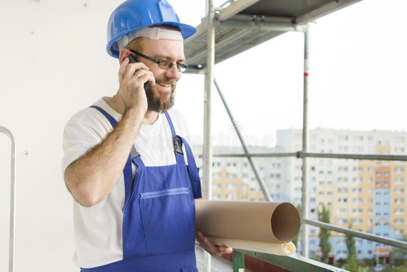 Рабочий-строитель в работая обмундировании и в шлеме стоя на большой возвышенности на строительной площадке с планами под его стоковое фото rf