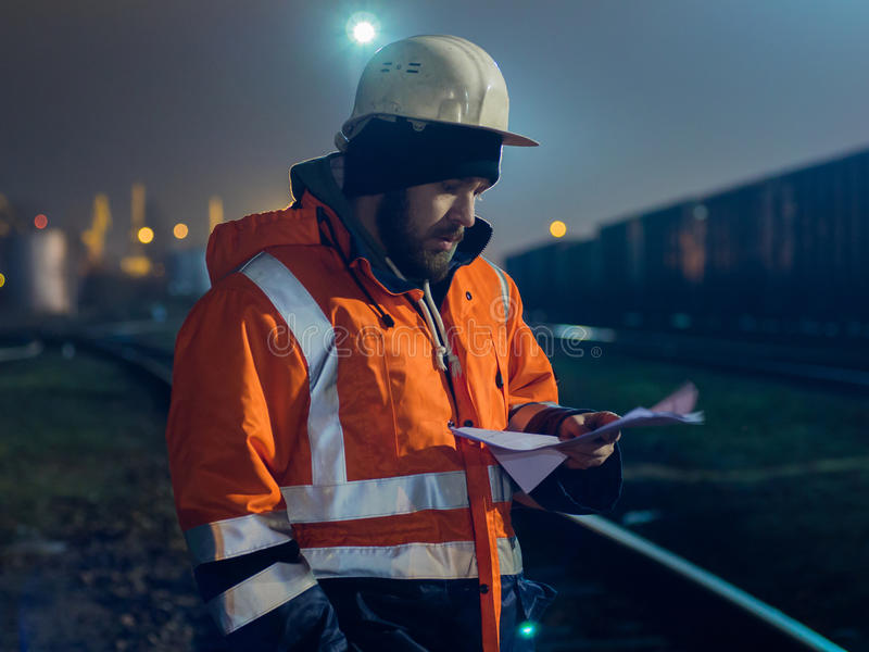 Рабочий-строитель в шлеме работая на ноче стоковая фотография rf