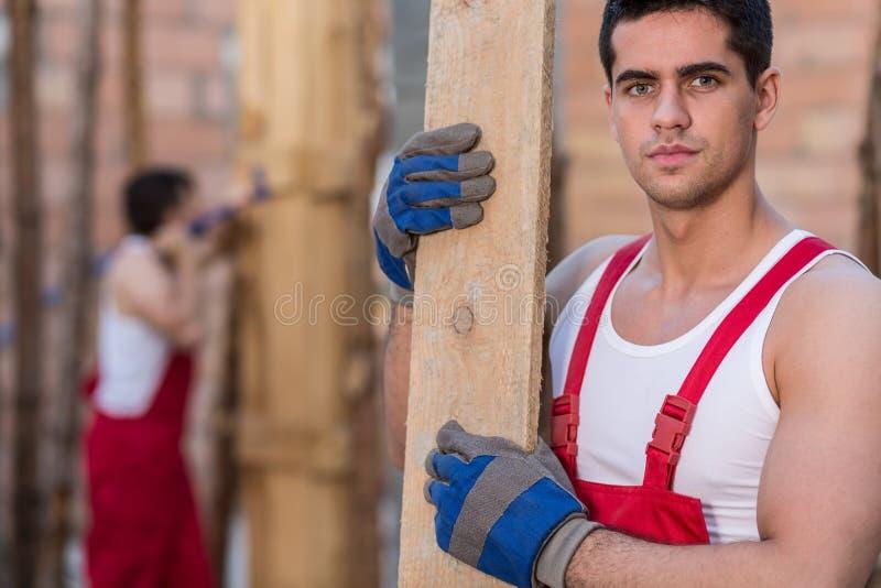 Рабочий-строитель держа деревянную планку стоковые изображения