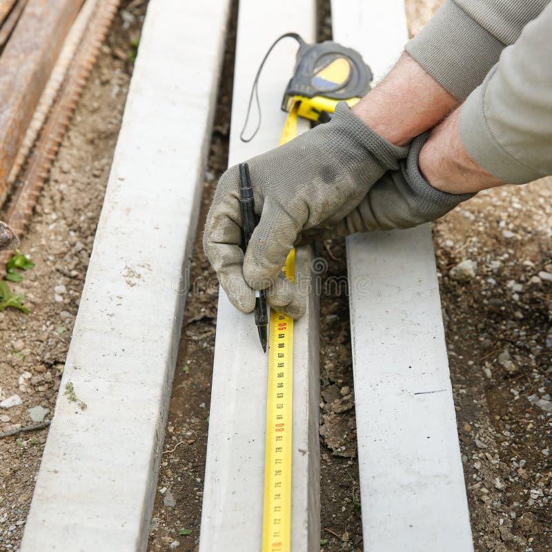 Рабочий-строитель измеряя конкретный штендер стоковые изображения rf