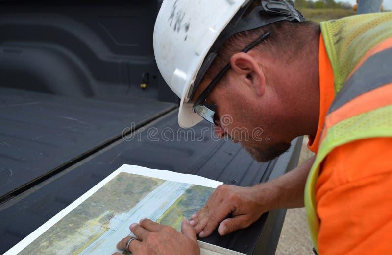 Рабочий-строитель используя инструменты стоковые фото