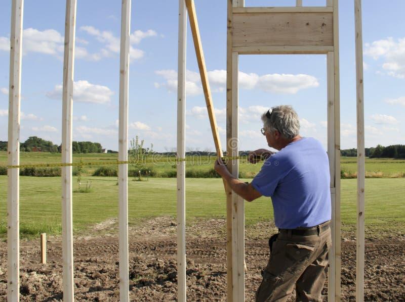 Рабочий-строитель используя правителя стоковое фото