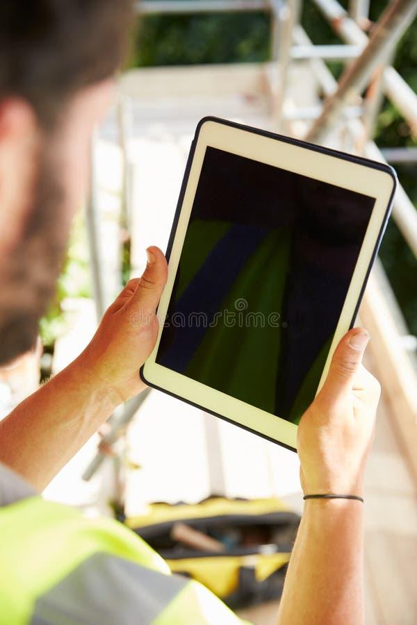 Рабочий-строитель используя таблетку цифров на строительной площадке стоковые изображения