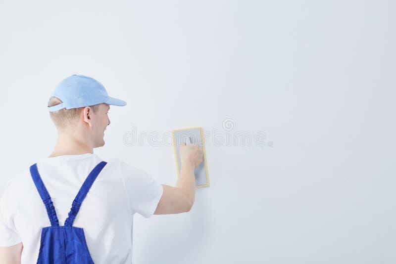 Рабочий-строитель и стена стоковое изображение