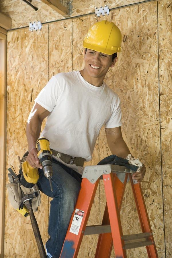 Рабочий-строитель на лестнице стоковые фотографии rf