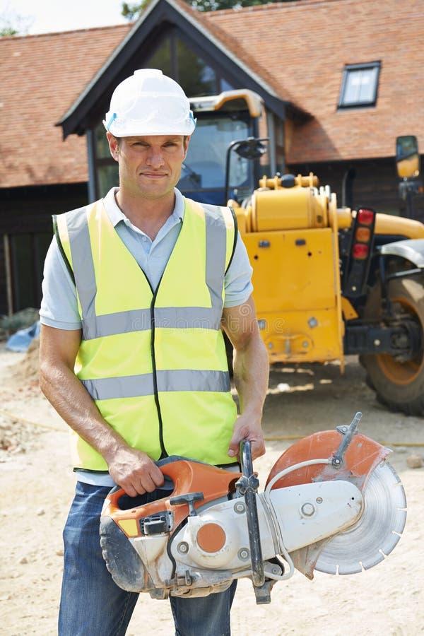 Рабочий-строитель на месте держа круглую пилу стоковое фото rf