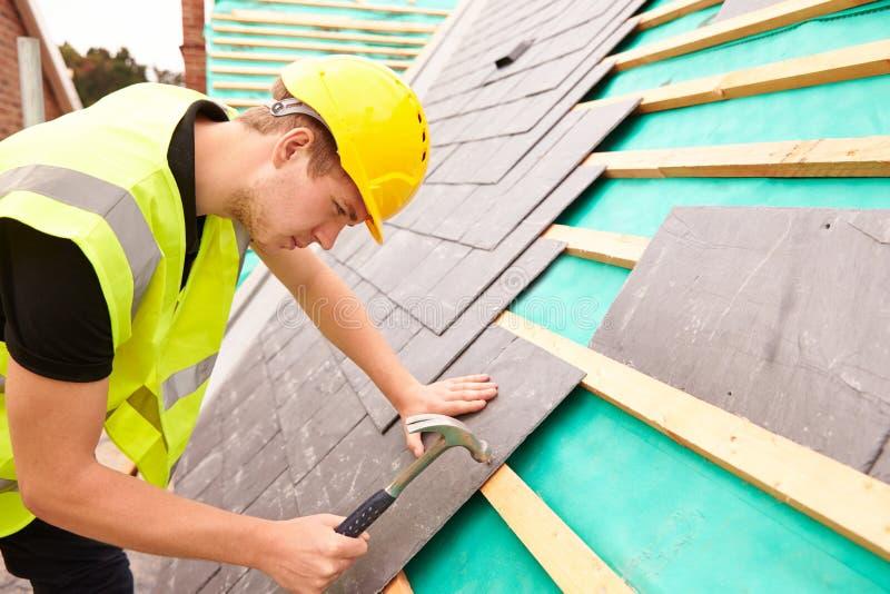 Рабочий-строитель на строительной площадке кладя плитки шифера стоковые изображения