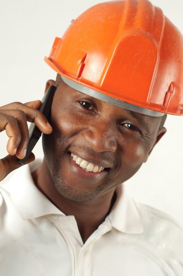 Рабочий-строитель на телефоне стоковая фотография