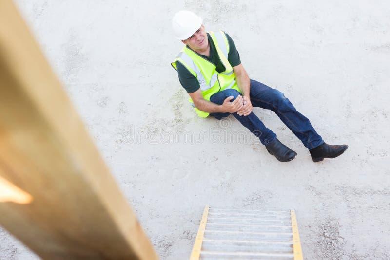 Рабочий-строитель падая лестница и повреждая ногу стоковые фотографии rf