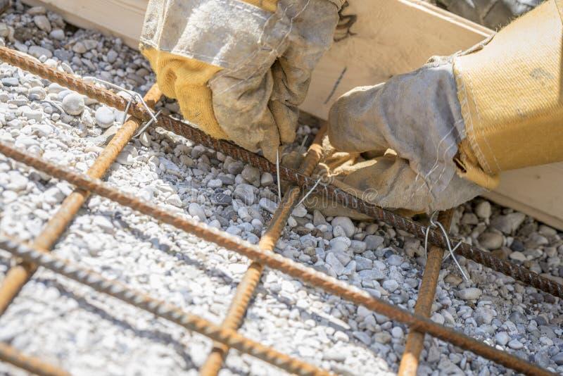 Рабочий-строитель связывая сталь усиливая штанги стоковая фотография rf