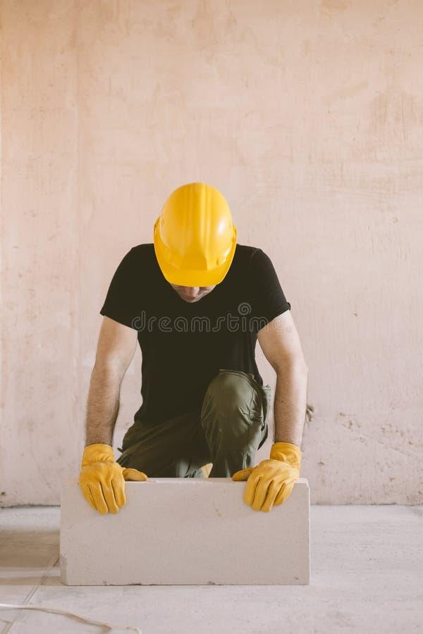 Рабочий-строитель с блоком стоковое фото
