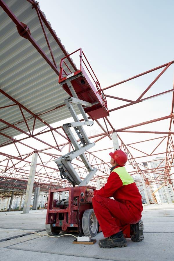 Рабочий-строитель с оборудованием подъема стоковые изображения rf