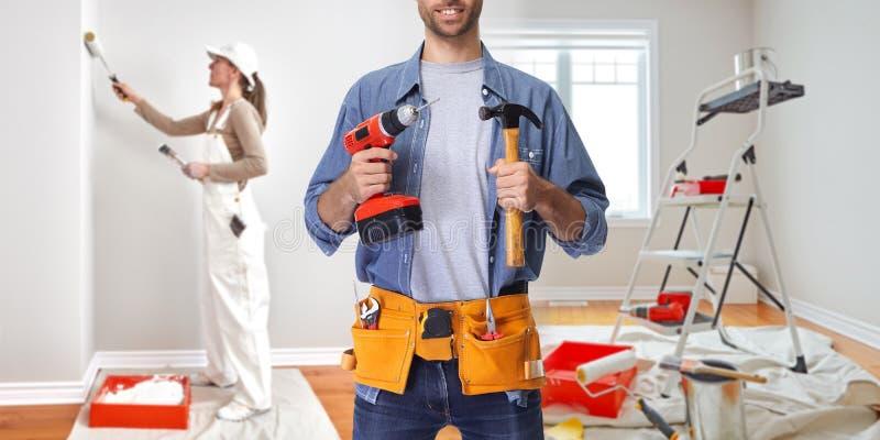 Рабочий-строитель с сверлом и молотком стоковые изображения