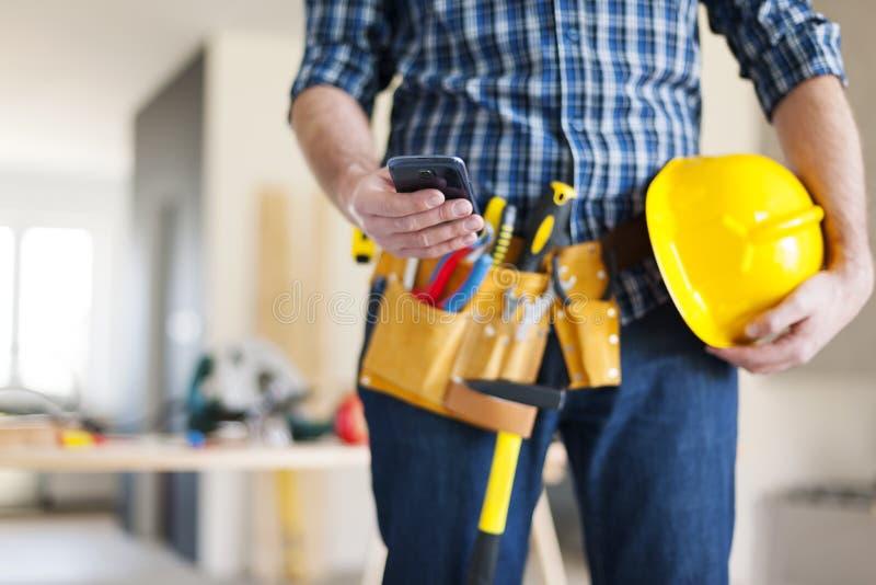 Рабочий-строитель с умным телефоном стоковая фотография