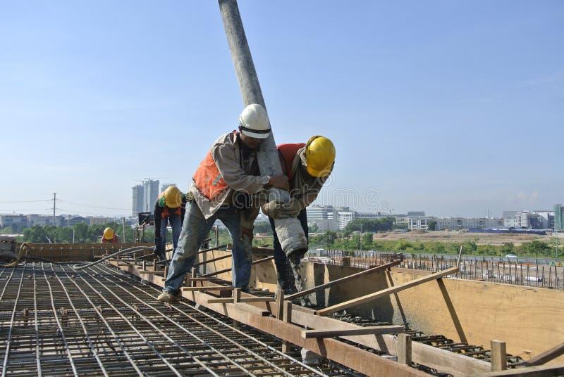 2 рабочий-строителя используя шланг от конкретного насоса стоковая фотография rf