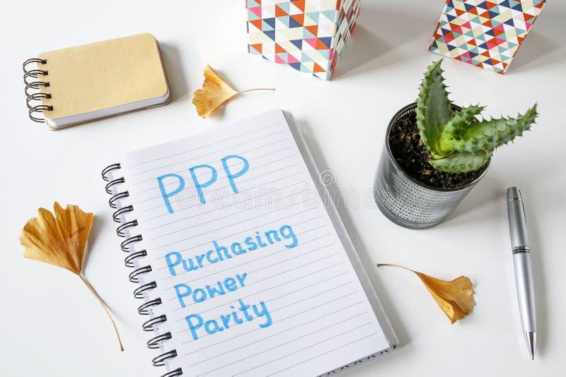 Равенство покупательной способности PPP написанное на тетради стоковые фотографии rf