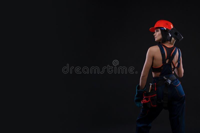 Равность и феминизм секса Назад сексуальной девушки держа молоток Деятельность женщины как механик стоковые фотографии rf