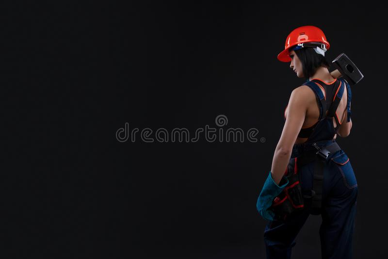 Равность и феминизм секса Назад сексуальной девушки держа молоток Деятельность женщины как механик стоковая фотография rf