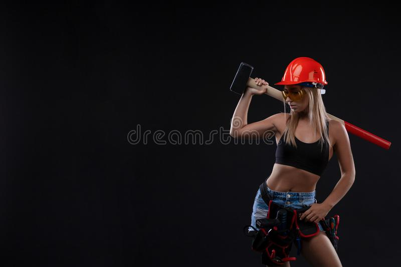 Равность и феминизм секса Сексуальная девушка в шлеме безопасности держа инструмент молотка Привлекательная деятельность женщины  стоковое изображение rf