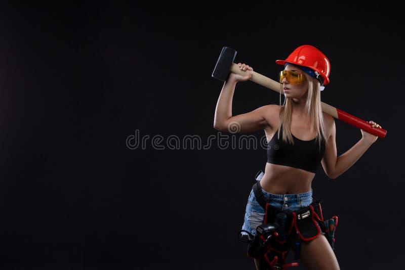 Равность и феминизм секса Сексуальная девушка в шлеме безопасности держа инструмент молотка Привлекательная деятельность женщины  стоковые фотографии rf