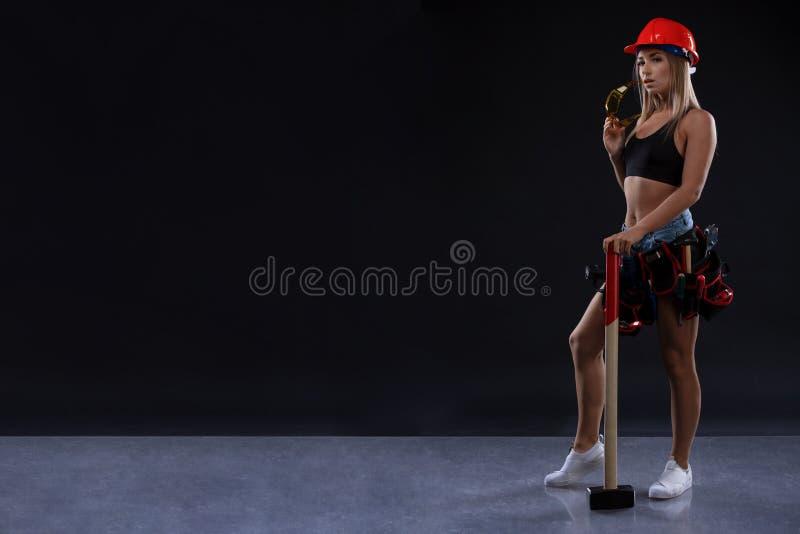 Равность и феминизм секса Сексуальная девушка в шлеме безопасности держа инструмент молотка Привлекательная деятельность женщины  стоковые изображения
