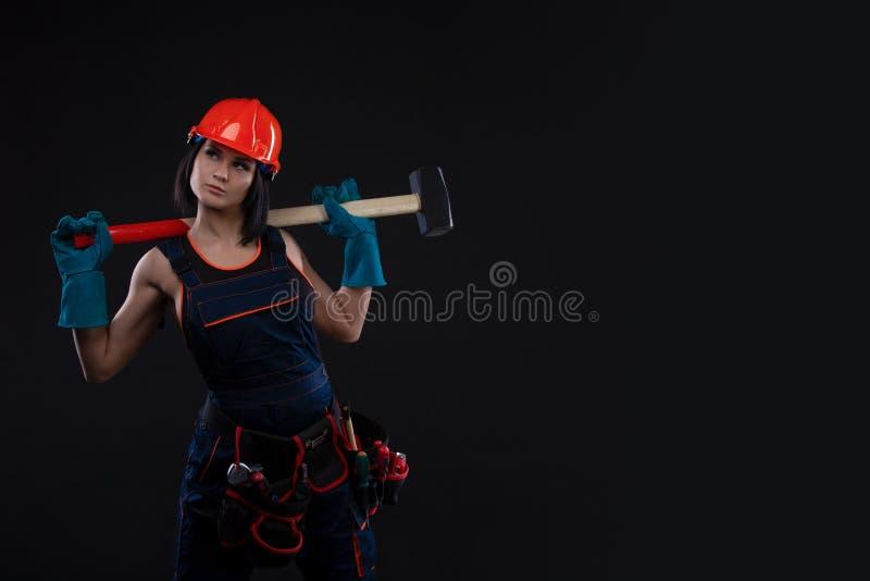 Равность и феминизм секса Сексуальная девушка в шлеме безопасности держа инструмент молотка Привлекательная деятельность женщины  стоковые изображения rf