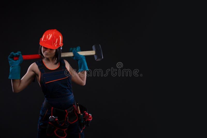 Равность и феминизм секса Сексуальная девушка в шлеме безопасности держа инструмент молотка Привлекательная деятельность женщины  стоковая фотография